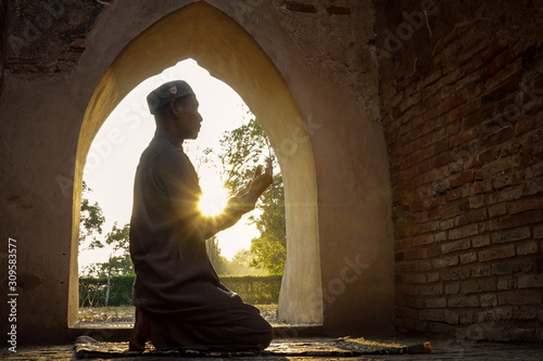 Fotomural  The silhouette of a muslim man Praying in an old mosque in Phra Nakhon Si Ayutth