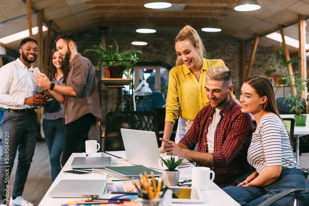 Fototapeta Creative team discussing new marketing strategy on laptop