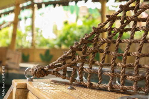Brown rope is a net attached to the iron ring on the wooden floor Wallpaper Mural