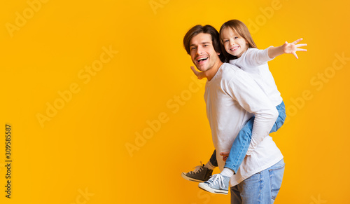Photo Cheerful daddy is holding his happy daughter on his back