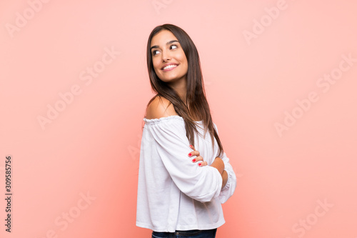 Young woman over isolated pink background with arms crossed and happy
