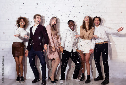 Positive Young People Standing Under Falling Confetti Having Fun Indoor