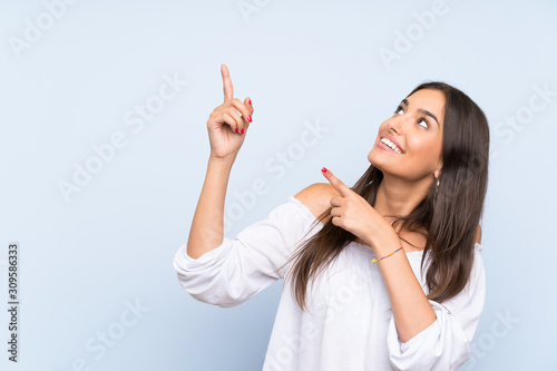 Obraz Young woman over isolated blue background pointing with the index finger a great idea - fototapety do salonu