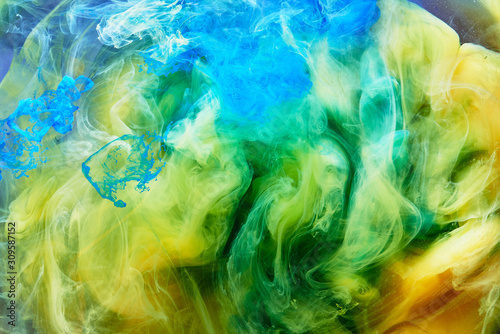 Abstract dancing colorful fume background. Clouds of smoke blue, green and ye...