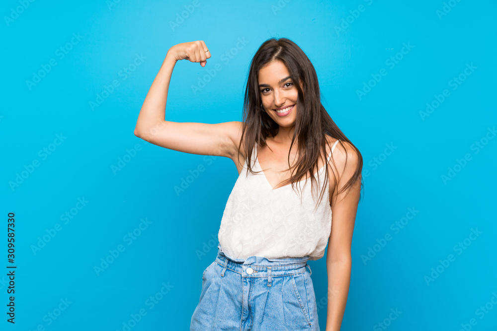 Fototapeta Young woman over isolated blue background doing strong gesture