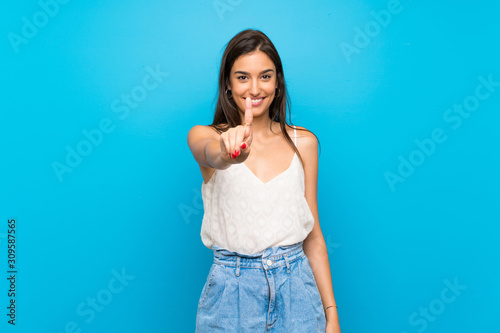 Young woman over isolated blue background showing and lifting a finger