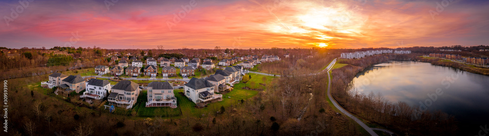 Fototapeta Aerial sunset panorama view of luxury upscale residential neighborhood gated community single family homes with decks and gazebos manicured green lawn lake view East Coast USA, American real estate