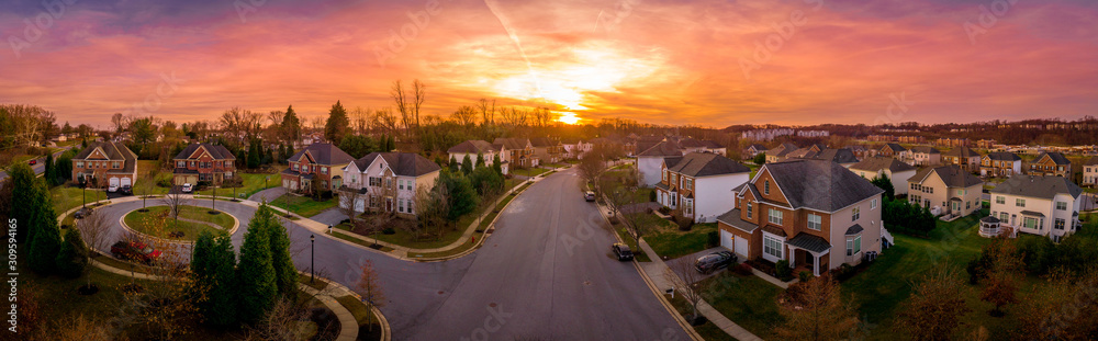 Aerial sunset panorama view of cul-de-sac (dead-end) luxury upscale residential neighborhood gated community street in Maryland USA, American real estate with single family homes brick facade