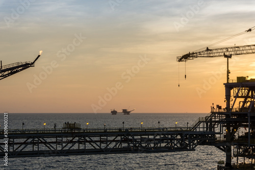 Silhouette of an oil production platform connected with a bridge at oil field during sunset