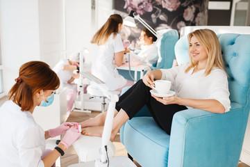 Two women on pedicure procedure in beauty salon