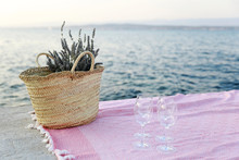 Nice Picnic Arrangement. Pink Banket By The Sea With Vine Glasses And Picnic Basket Filled With Lavender.