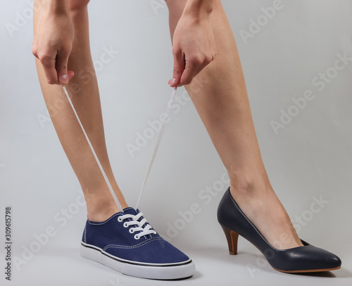 Canvas Print Slim woman's legs in two different shoes with heels and sneakers on white background