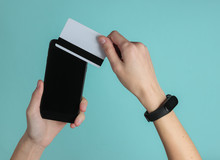Hand With Smart Bracelet Holding Bank Card And Smartphone  On Blue Background. Cashless Payment, Online Shopping. Top View.