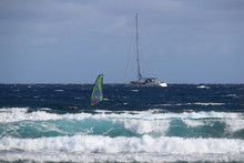 Selective Focus On Sailing Yacht On Choppy Sea Behind Windsurfer And Turquoise Waves