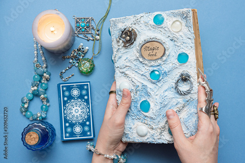 Fortune teller holding in hands a white magic book on blue background. © Natali