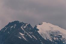 Mountain Range Under Cloudy Sky. Snowy Peaks Of Mountains Rocks