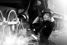 Beautiful Girl In A Black Dress And Hat Near An Old Steam Locomotive And Big Iron Wheels. Blond Beauty. Vintage Portrait Of The Last Century, Retro Journey.