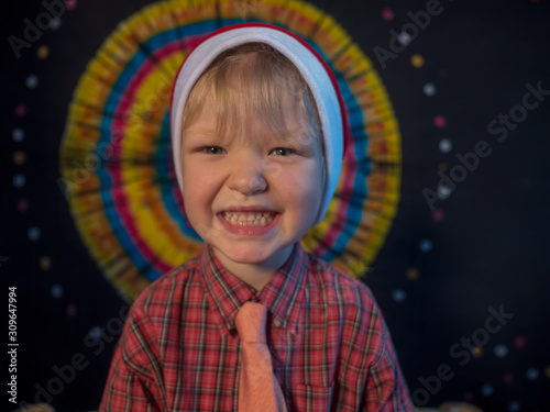 Photo charming little boy is sitting in festive attire next to luminous and blinking Christmas lights