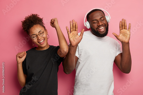 Horizontal shot of happy black woman and man move with rhythm of music, have fun indoor, dance on party, have carefree glad faces, isolated over pink background. People, emotions, amusement. - 309654373
