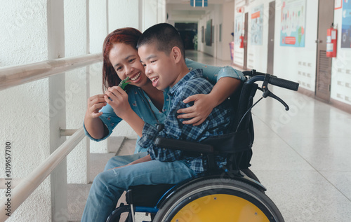 Fotomural Mother and Asian special child on wheelchair is smile happily on background in school corridor, Life in the education age of disabled children, Happy disabled kid concept