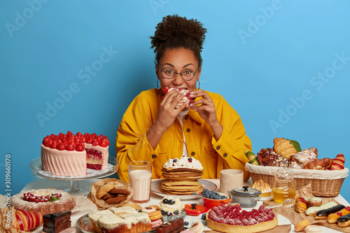 Fotografía Funny glutton woman bites cakes with big appetite, cant stop eating sweet desser