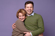 Happy Mother And Her Son Hugging Standing At Studio On Colored Background. Studio Shot