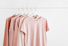 Feminine Clothes In Pastel Pink Color On Hanger On White Background. Spring Cleaning Home Wardrobe. Minimal Fashion Concept.