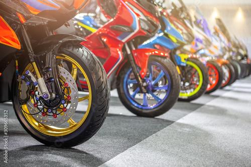 Motocykle zaparkowane na parkingu dla motocykli, Zbliżenie na przednie koło motocykli.