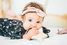 Beautiful Baby Girls With A Bow On Her Head Chews Wooden Stars. Six Month Baby Girl Chewing Wooden Teething Toy.