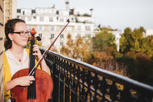 Young Smiling Female Cellist Plucking Cello Strings On A Beautiful Balcony