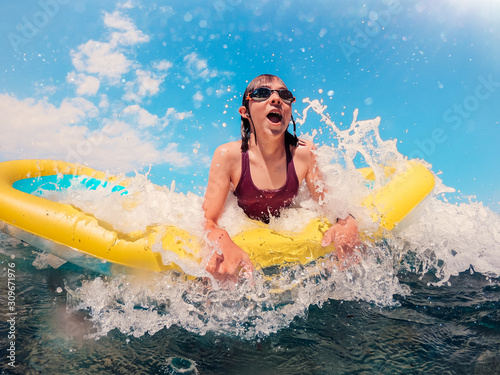 Fototapeta Girl on floating inflatable airbed getting splashed by the wave