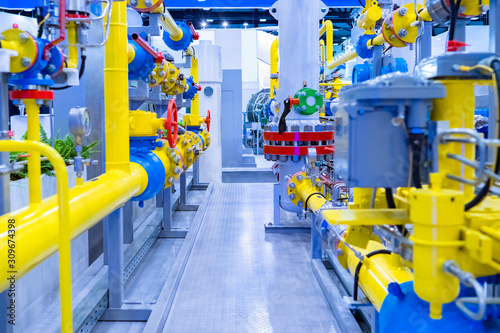 Fototapeta Gas distribution room at the enterprise. Yellow-blue pipes. Industrial equipment. Installation for pumping gas. Gasification of an industrial enterprise. Stationary compressor station. obraz