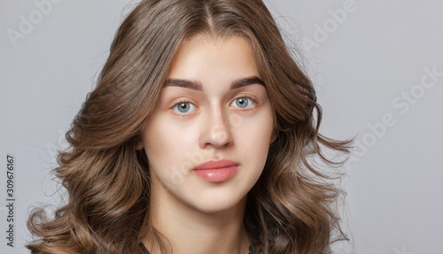 Fotografía Portrait of a beautiful happy woman with curly hair, clean skin and thick eyebrows  beauty salon