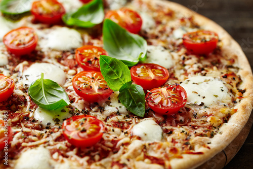 Tasty pizza with cherry tomatoes and fresh basil. Close up. Canvas Print