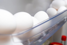 Many White Chicken Hen Eggs On A Shelf Of A Frige Door Close Up