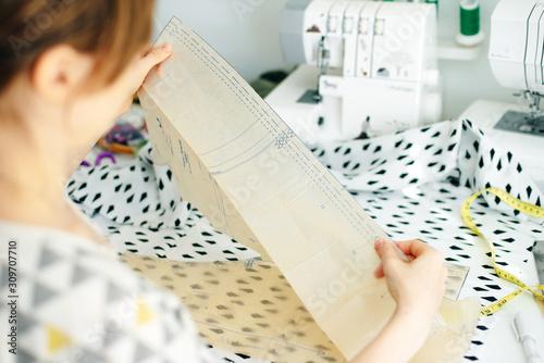 Fototapeta Top view of workplace of seamstress. Dressmaker cuts detail on sketch. Seamstress cuts pink fabric with scissors obraz