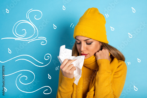 Girl caught a cold and wipes her nose. Cyan background Wallpaper Mural