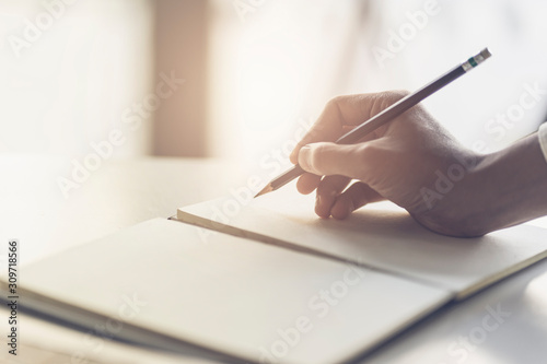 Close up of male hand writing with pencil on the book. Businessman working with data information in the office.