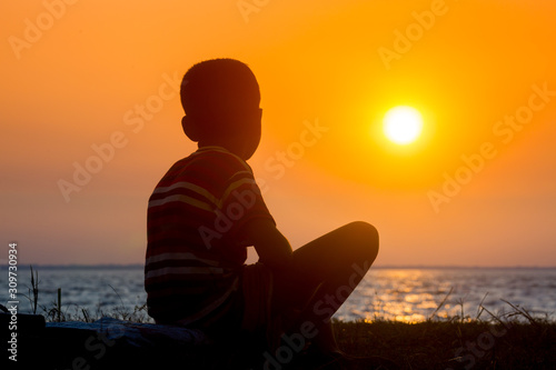 Fototapeta A crippled child sitting at the river watching the sunset