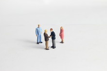 Gray Backgrond, Simple Illustration Photo For Mini Figure Two Man Toy Handshaking For Business Agreement Beyond Their Partner