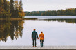 Couple in love holding hands romantic dating family lifestyle relationship man and woman standing on pier outdoor enjoying lake and autumn forest landscape