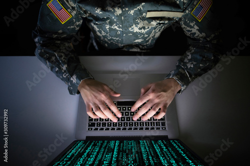 Obraz American soldier in military uniform preventing cyber attack in military intelligence center. An US officer intercepting messages to stop terrorism. Modern warfare system surveillance concept. - fototapety do salonu