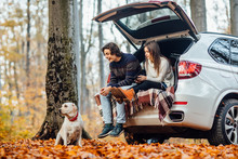 Young Couple Have A Picnic With Their Dog Near Automobile In The Forest.