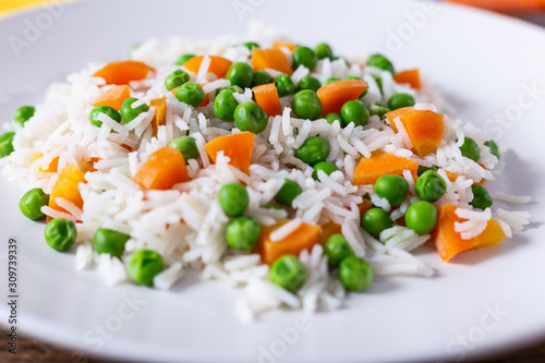 Photo Basmati rice with carrots and green peas. Close up view.