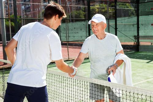 Obraz na plátně  senior and young man shake hands before padel tennis match
