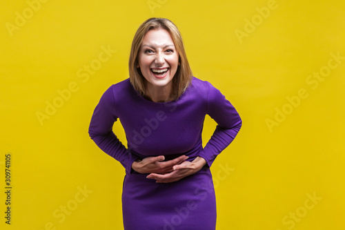 Portrait of joyous positive woman in elegant tight purple dress holding her hands on belly and can't stop laughing hard, hearing funny stories, joke Canvas Print