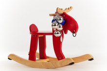 Wooden Toy Rocking Chair Red Moose Decorated With Christmas Toys On A White Background In The Studio. Concept Of Christmas Gifts For Children. Advertising Space
