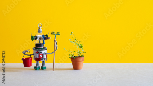 Photo  Creative design steampunk toy gardener with bucket rake and plant in clay flower pot