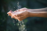closeup water flow to hand of women for nature concept on the garden background.