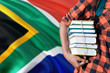 canvas print picture - South Africa national education concept. Close up of teenage student holding books under his arm with country flag background.